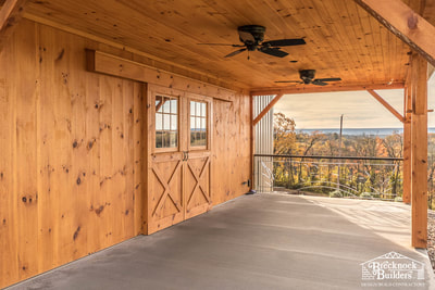 Wood-siding country market with sliding doors by Brecknock Builders