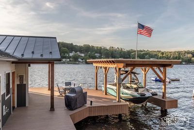 Boat dock connected to lake-house with metal roof.
