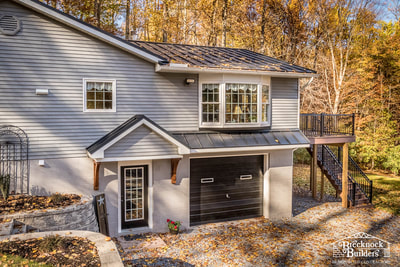 Major remodel by Brecknock Builders with new siding and Black Metal Roof