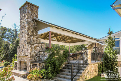 Custom deck and pavilion with stone fireplace and exposed beams